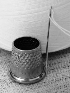 image of thimble needle and thread used for our clothing alteration service