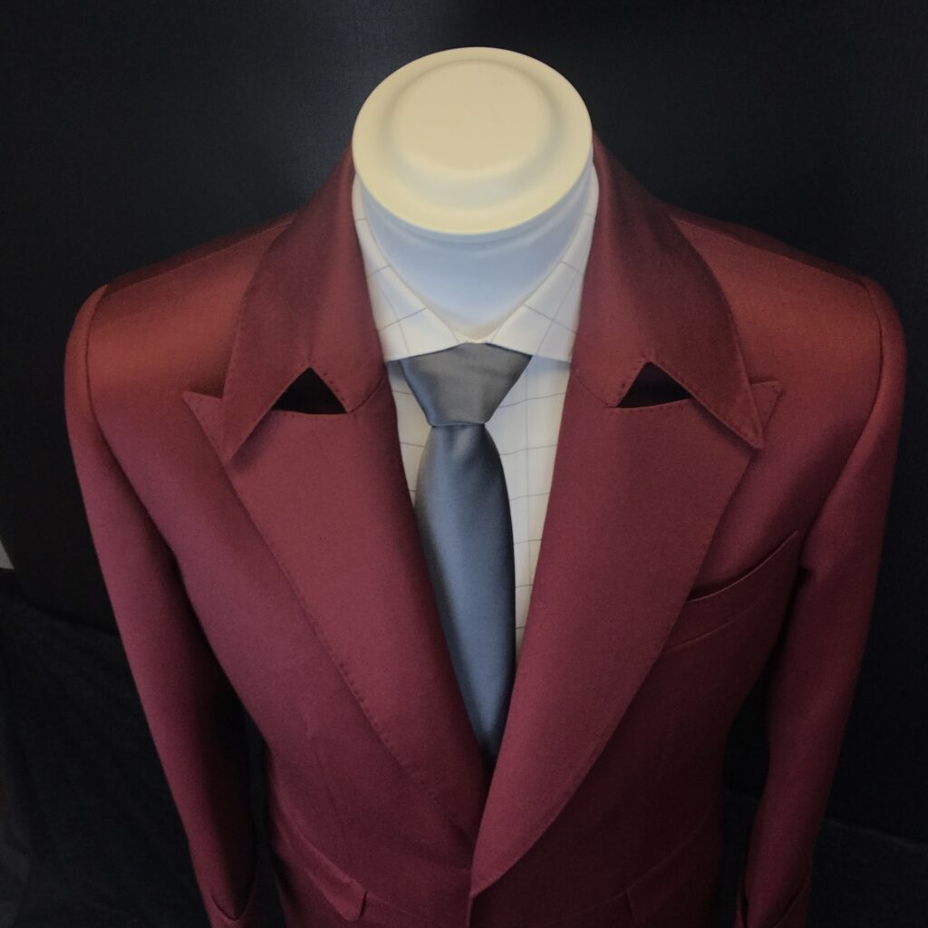 downward angle image of bespoke tailored red coat with oversized collar and lapels